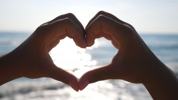 Žena dělá srdce skrz ruce s mořskou pláštěnkou v pozadí. Detailní záběr ženských paží se symbolem lásky. Dáma odpočívá v letovisku a užívá si krásný den na pobřeží. Koncept letní dovolené.