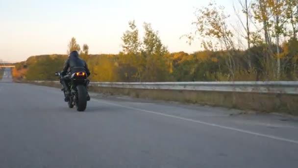Nerozpoznatelný muž v helmě jezdí rychle na moderní sportovní motorce na dálnici. Motorkář závodní jeho motocykl na venkovské silnici. Chlápek, co jezdí na kole. Pojem dobrodružství. Zadní pohled