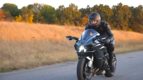 Motorcyclist racing his motorcycle on autumn country road. Young man in helmet riding fast on modern sport motorbike at highway. Guy driving bike during trip. Concept of freedom. Front view Close up