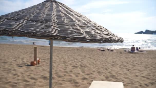 Gyönyörű kilátás nyílik a tengerre és a homokos strand szalma napernyővel nyáron. Felismerhetetlen turisták pihennek a tengerpart közelében és élvezik a nyári utazást. Nyugodt idilli jelenet az óceán partjainál