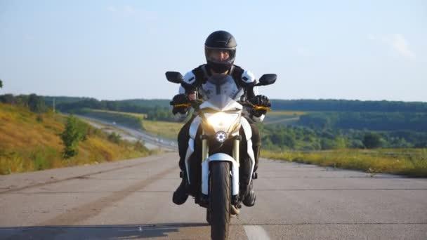Muž v helmě řízení silný sportovní motocykl na dálnici s krásným pozadím. Motocyklista rychlost na motocyklu s reflektorem podél venkovské silnice. Mladý muž si užívá rychlost. Koncept svobody