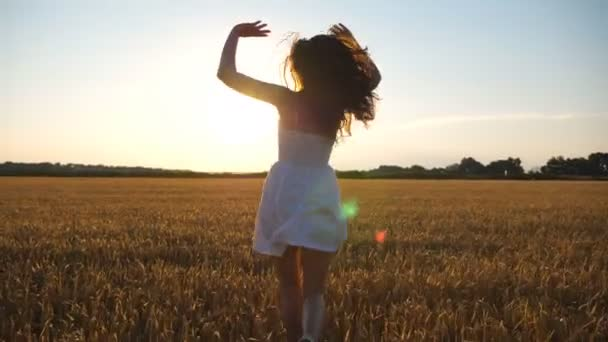 Attractive joyful woman in white dress running through field of wheat at sunset. Follow to young carefree girl enjoying freedom in beautiful nature environment. Scenic summer landscape with sundown