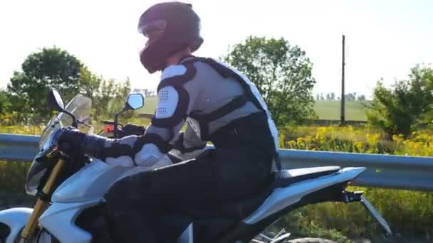 Muž v helmě jezdí rychle na výkonné sportovní motorce na dálnici. Motorkář závodní jeho motocykl na venkovské silnici. Chlápek s motorovým vybavením jezdí na kole. Koncept dobrodružství a svobody