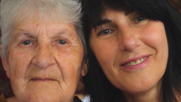 Portrét starší ženy s dospělou dcerou, jak se dívá do kamery a ukazuje radostné emoce. Šťastné ženy se usmívají a užívají si rodinných vztahů. Uzavření pomalého pohybu