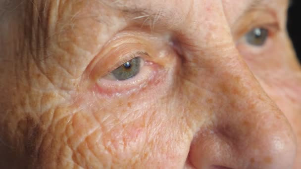 Portrait of elderly woman watching pensive to something. Close up of female eyes with wrinkles around. Grandmother looking calmly into distance and thinking. Slow motion Detail view