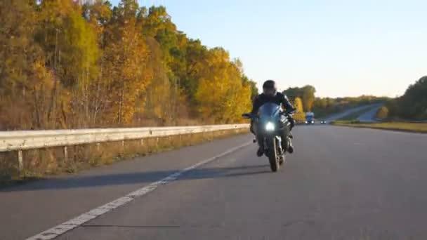 Mladý muž jede rychle na moderní sportovní motorce na podzimní dálnici. Motorkář závodní jeho motocykl na venkovské silnici. Chlápek, co jezdí na kole. Pojem svoboda a dobrodružství. Pohled zepředu