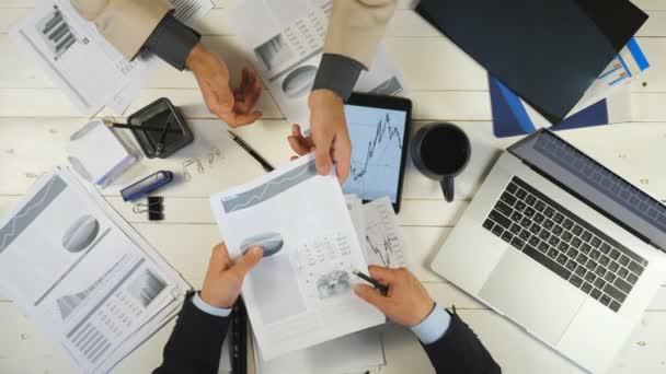 Von oben männliche Hände zweier junger Geschäftsleute, die im Amt Diagramme prüfen und Finanzberichte diskutieren. Erfolgreiche Geschäftspartner sitzen mit am Tisch und entwickeln ein neues Geschäftsprojekt
