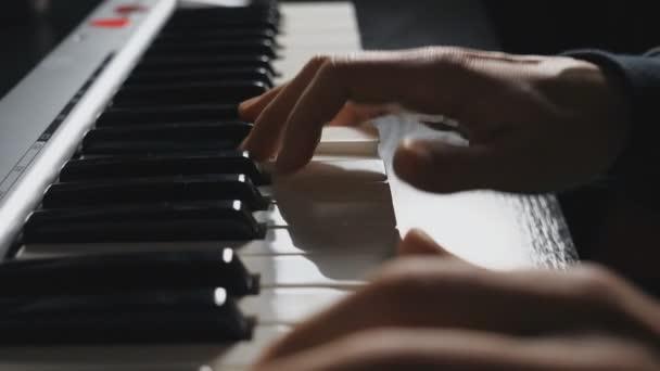 Finger des Pianisten drücken auf Synthesizertasten. Menschenhände spielen Solo-Musik am Klavier. Zeitlupe Draufsicht Nahaufnahme