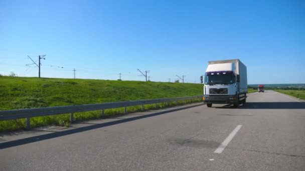 Camera follows to truck with cargo trailer driving on highway transporting goods at summer day. White lorry riding through countryside with beautiful landscape at background. Slow motion Front view