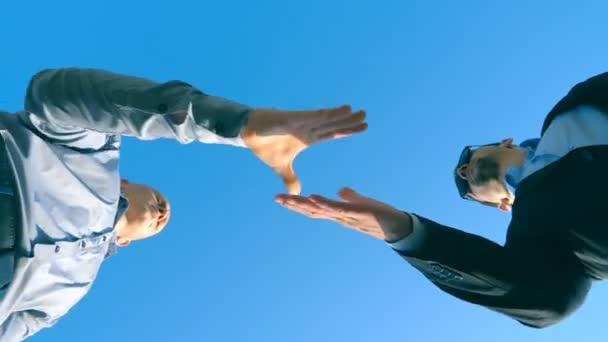 Mladý prodavač formální oblek pozdrav s mužské kupující a dávat mu klíče od auta na pozadí modré oblohy. Handshake mezi dvěma podnikateli. Koncept prodeje a nákupu doprava. Nízký úhel pohledu