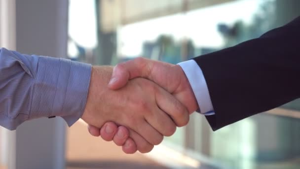 Dva mladí kolegové potřesení rukou po úspěšné řešení poblíž kancelářská budova. Důvěru podnikatele gratulací navzájem v městském prostředí. Handshake obchodních partnerů. Boční pohled zblízka