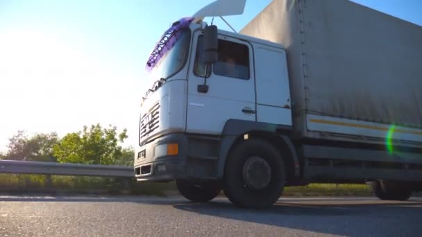 Truck driving on a highway. Lorry rides through the countryside with sunset at background. Bottom Side view Slow motion Close up