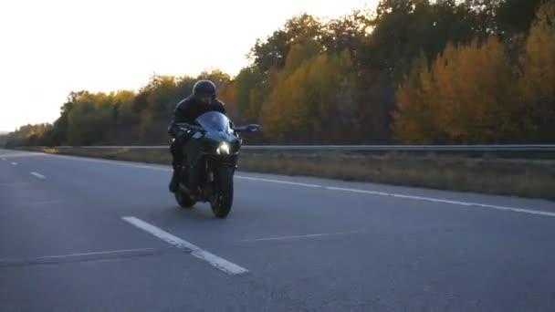 Muž v helmě jezdí rychle na moderní sportovní motorce na dálnici. Motorkář závodní jeho motocykl na venkovské silnici. Chlápek, co jezdí na kole. Pojem svoboda a dobrodružství. Boční pohled Zavřít