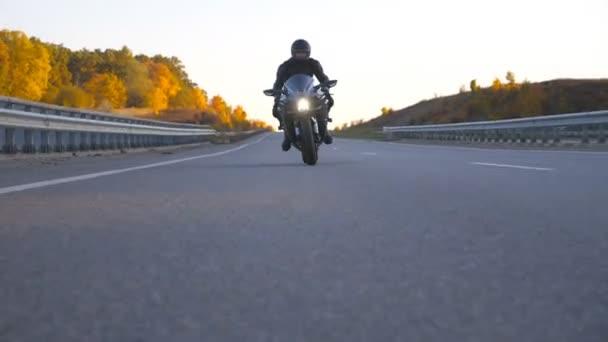 Přední pohled na mladého muže v helmě jezdí rychle na moderní sportovní motorce na dálnici. Motorkář závodní jeho motocykl na venkovské silnici. Chlápek, co jezdí na kole. Koncept svobody a dobrodružství