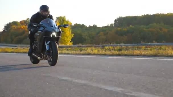 Motorkář závodní jeho motocykl na podzimní venkovské silnici. Mladý muž v helmě jezdí rychle na moderní sportovní motorce na dálnici. Chlápek, co jezdí na kole. Koncept svobody a dobrodružství