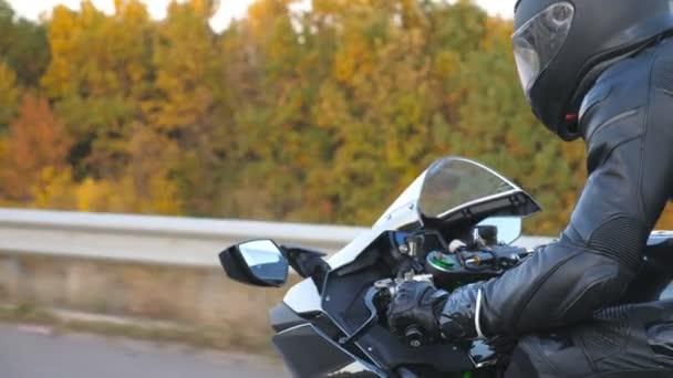 Detailní záběr motocyklista závodní jeho motocykl na podzimní venkovské silnici. Mladý muž v helmě jezdí na moderní sportovní motorce na dálnici. Chlápek, co jezdí na kole. Koncept svobody a dobrodružství