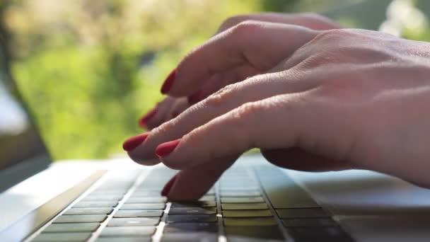 Női kezek gépelnek valami szöveget a laptop billentyűzetén. Egy nő, aki a szabadban dolgozik a notesznél. Csevegni valakivel, netezni. Kreatív szabadúszó használ pc a természetben. Homályos háttér