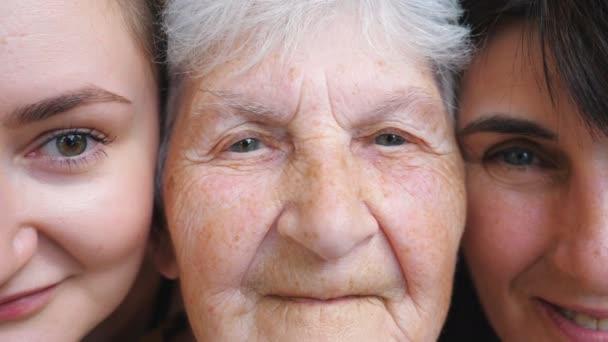 Portrét postarší ženy s dcerou a vnučkou, jak se dívají do kamery a usmívají se spolu. Šťastné dámy projevující radostné emoce na tvářích. Pozitivní výraz obličeje žen. Zavřít
