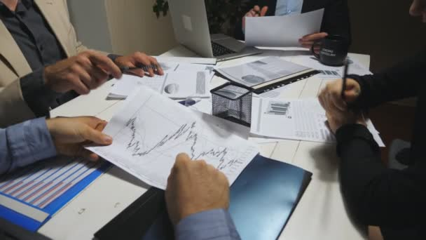 Male and female hands of coworkers examining graphs at the end of working day. Business team sitting at table and analyzing financial reports. Business people checking documents at desk. Top view