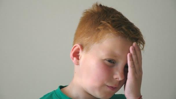 Portrét vážného zrzavého hocha s pihami. Zoufalý kluk myslí na své problémy uvnitř. Zblízka emoce mužského dítěte se smutným výrazem na tváři. Zpomalený pohyb