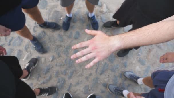 Von oben betrachtet stapeln sich die Hände junger Athleten nacheinander zu einer Einheit. Gruppe bester Freunde, die ihre Arme in die Mitte eines Kreises legen und sie hochheben. Konzept der Freundschaft und Teamarbeit. Langsames Wachstum