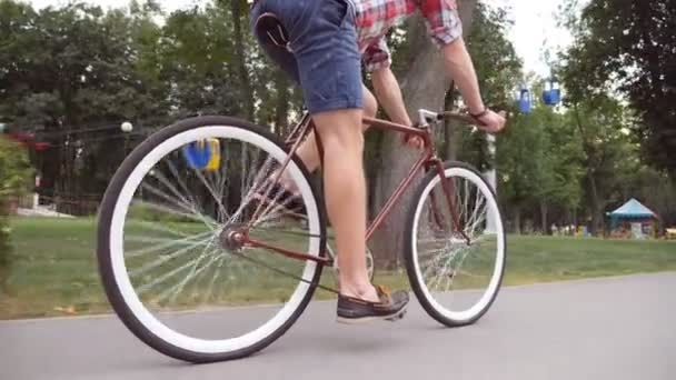 Egy fiatalember biciklizik a park útjánál. Sportos srác kerékpározik a szabadban. Egészséges, aktív életmód. Alacsony látószög Bezárás Lassú mozgás
