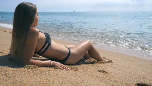 Schöne kaukasische Frau entspannen an der Küste während der Sommerferien reisen. Junges Mädchen im Bikini liegt am Strand und sonnt sich. Konzept der Erholung an der Küste des Resorts. Zeitlupe Nahaufnahme