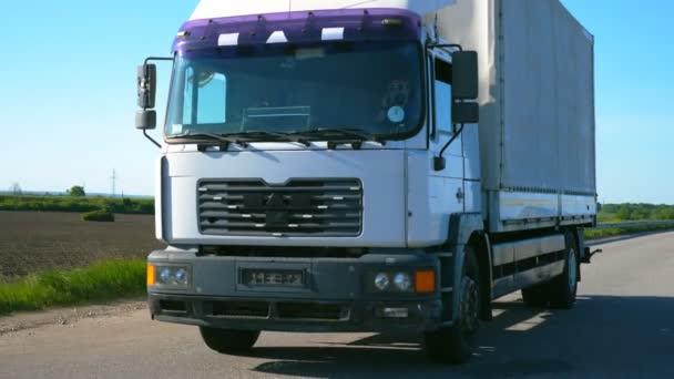 Kamera následuje kamion s nákladním přívěsem jedoucím po dálnici a převážejícím zboží v letní den. Nákladní automobil projíždí krajinou s přírodou v pozadí. Pomalý pohled zepředu Zavřít