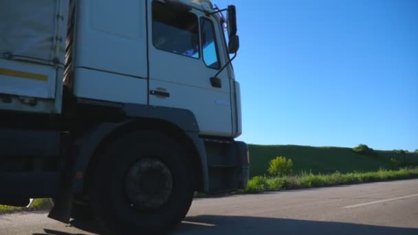 Camera follows to truck with cargo trailer driving on highway and transporting goods at sunny day. White lorry speeding through country road riding to destination. Slow motion Side view Close up