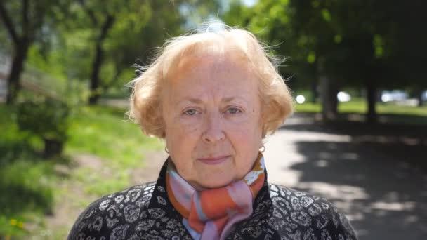 Porträt einer schönen älteren Frau, die ernst und nachdenklich in die Kamera blickt. Eine ältere kaukasische Dame im Rentenalter steht im Hintergrund der Stadt. Anblick der Großmutter im Freien. Nahaufnahme