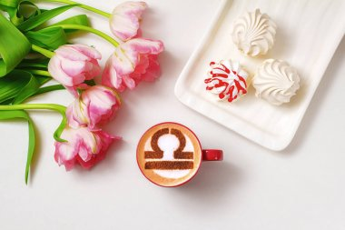 white cup of coffee with the symbol of the zodiac Libra on milk foam