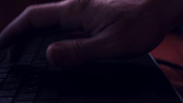 Männliche Hand berührt schwarzen Laptop