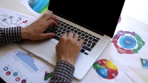 Člověk pracující s přenosným počítačem v kanceláři