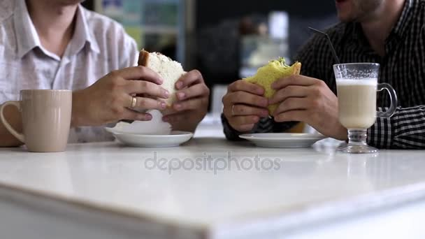Business lunch. Two men eating sandwiches