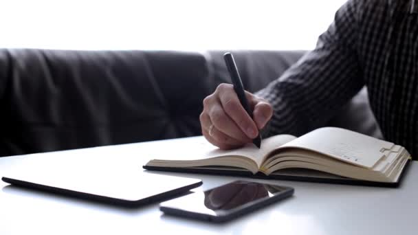 Man takes notes in a notebook