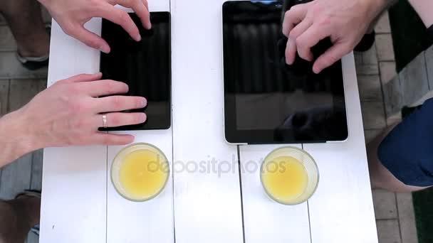 Muži pracují s tablety v kavárně