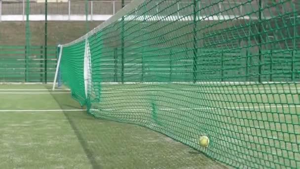 Kamera se pohybuje podél sítě tenisového kurtu, do kterého míčky padají