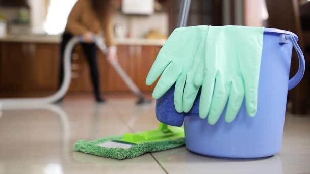 Čisticí prostředky pro domácnost. Dívka tančí s vysavačem v ruce čistí podlahu v kuchyni