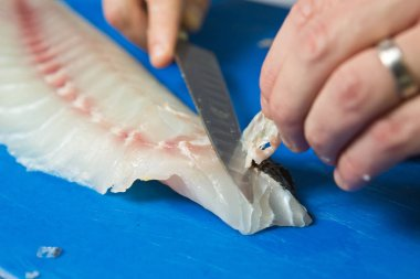 Filleting and removing the bone from a fresh fish on a blue cutting board using a sharp knife.