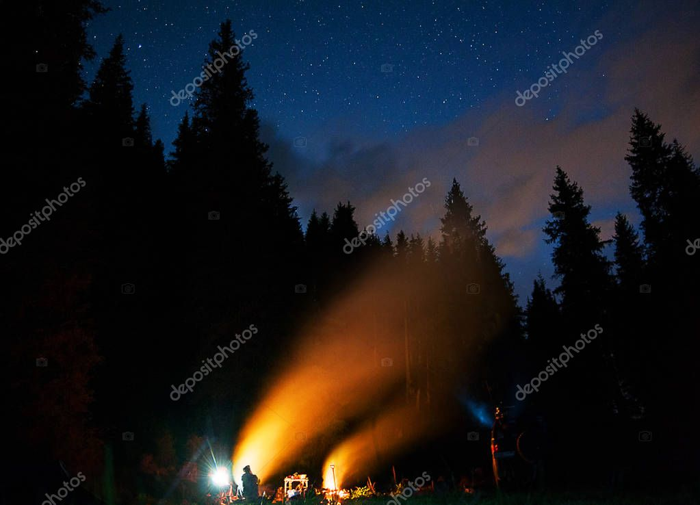 The company of young people are sitting around the bonfire and singing songs. Tourist camp under starry night sky . Travel concept