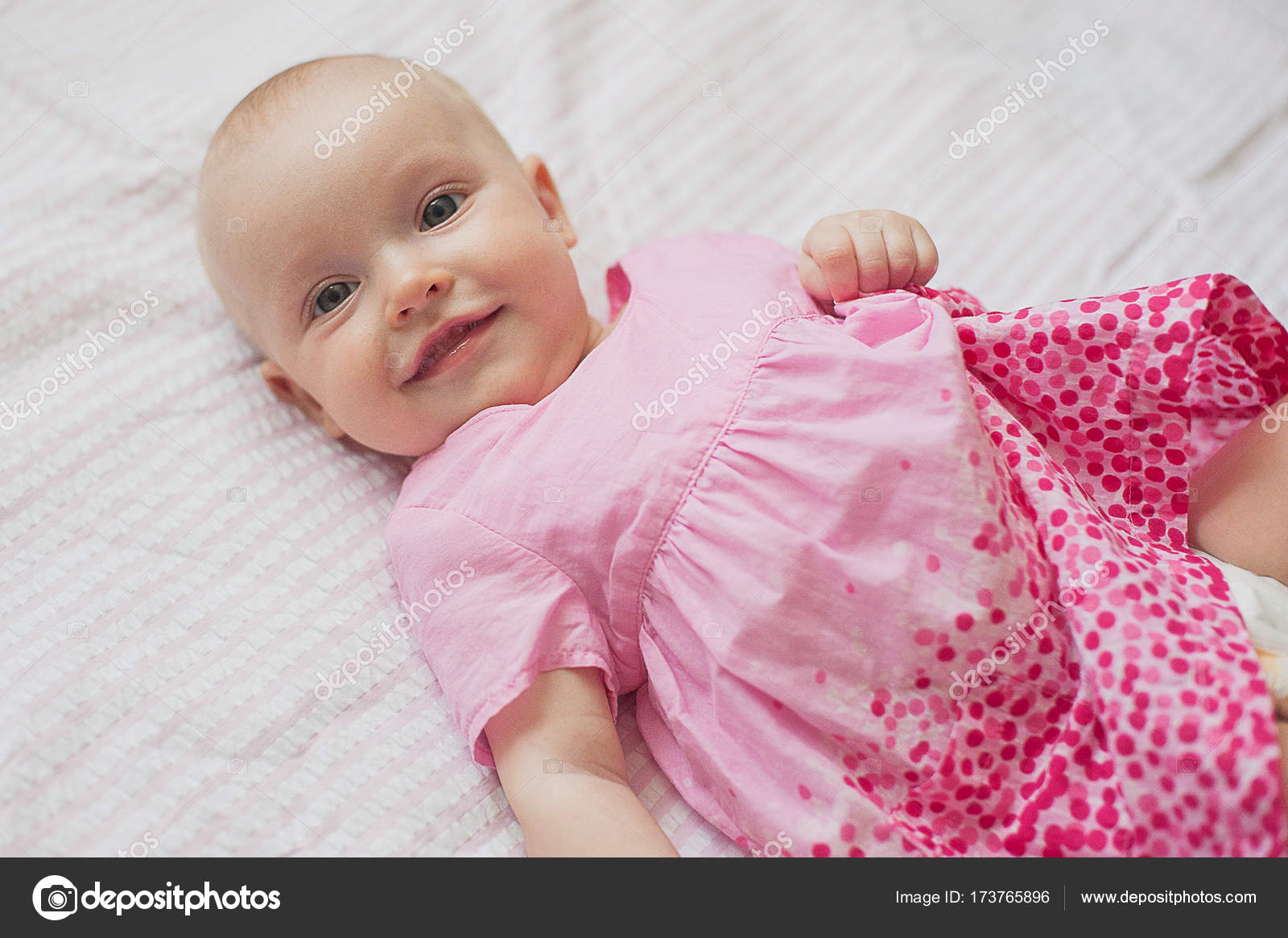 789fdcf36 Cute baby girl in pink dress lies on white backgroun. Close-up ...