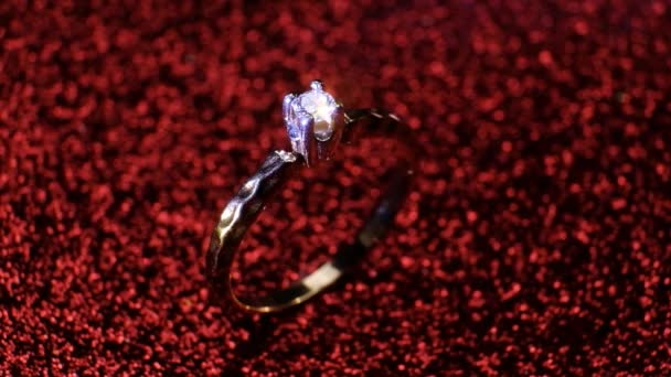 Beautiful shiny golden engagement ring with big gem diamond on glitter red background. st Valentines Day present. Marriage proposal for February 14