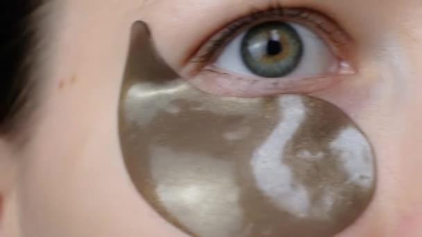 Krásná žena se dívá na kameru s kolagenem hydrogel pásky do očí. Jak aplikovat kosmetické náplasti pod oči. Skincare.