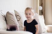 Távolságtanulás, online oktatás gyerekeknek. A kislány otthon tanul az okostelefon előtt. Gyerek online rajzfilmeket néz, gyerekek számítógép-függőség, szülői felügyelet. Karantén otthon