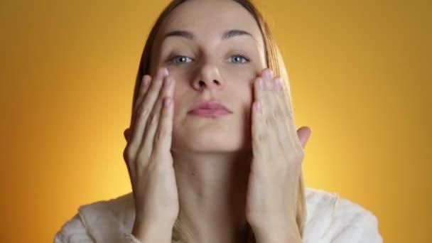 Krásný model dát krém na obličej na žlutém podkladu