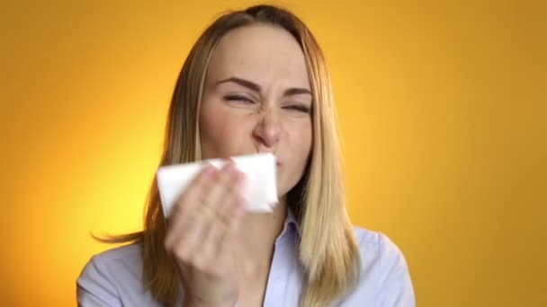 Sick woman blowing his nose into tissue on a yellow background