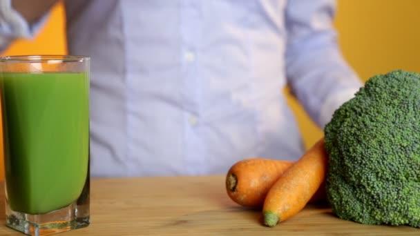 zdravé výživy, vegetariánské jídlo, dieta a detox koncept - žena ruku dát sklenice Mrkvová šťáva na stole se zeleninou