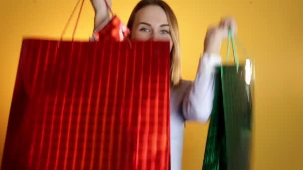 Nákupní žena šťastná usmívající se hospodářství nákupní tašky izolované na žlutém podkladu. Krásné čerstvé mladé Smíšené rasy asijského kavkazských modelka