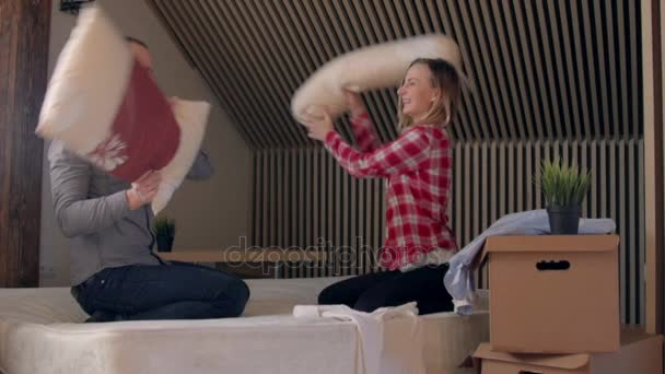 Young couple having a pillow fight in a home bedroom