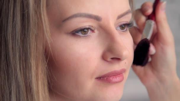 Oční make-up žena použití eyeshadow prášek. Krásná žena tvář. Dokonalý make-up. Módní krása. Řasy. Kosmetické oční stíny. Detailní záběr.